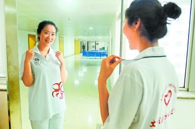 月19日,长沙青年志愿者周立婧开心地穿上第七届中博会志愿者服