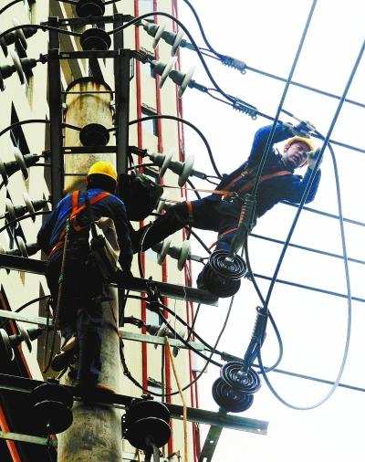 1月13日,宁远县城九嶷中路,电力工人冒着严寒调整线路负荷.